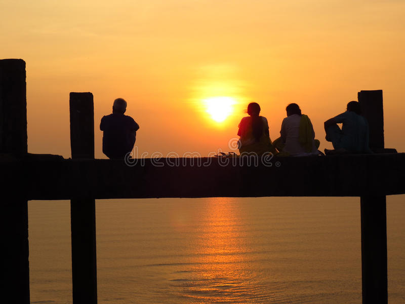 Serene Vacation. Silhouette of four friends enjoying the sunset on a platform over the sea