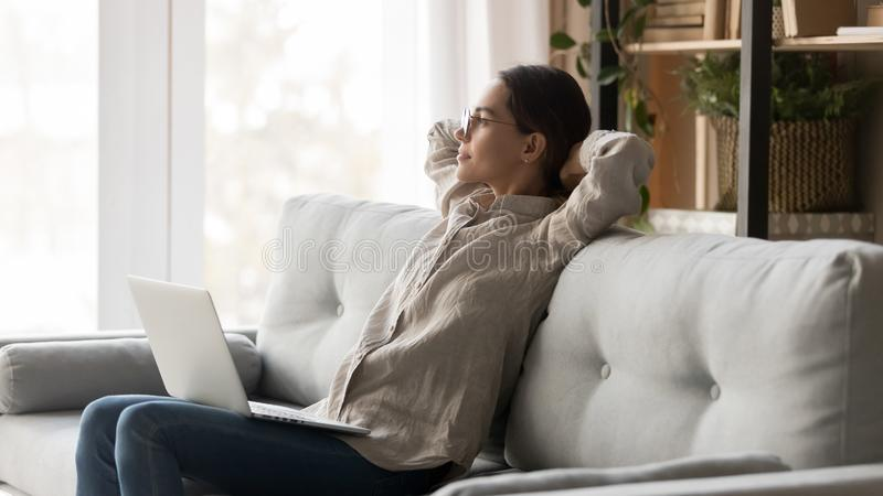 Serene woman with computer on laps leaning on couch resting royalty free stock photography