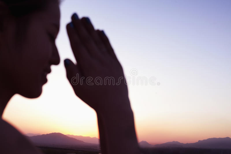 Serene young woman with eyes closed and hands together in prayer pose in the desert in China, focus on background royalty free stock image