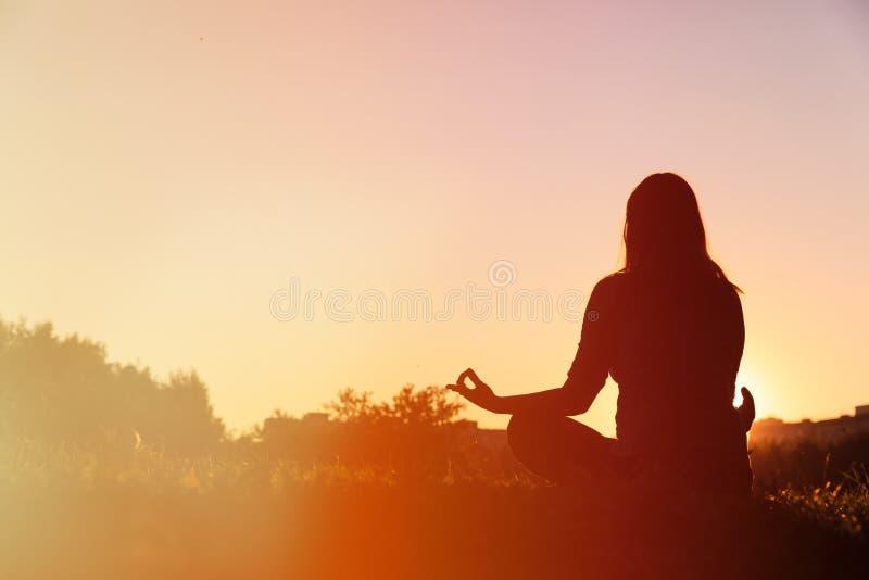 Serenitet- och yogaövning på solnedgången royaltyfri fotografi
