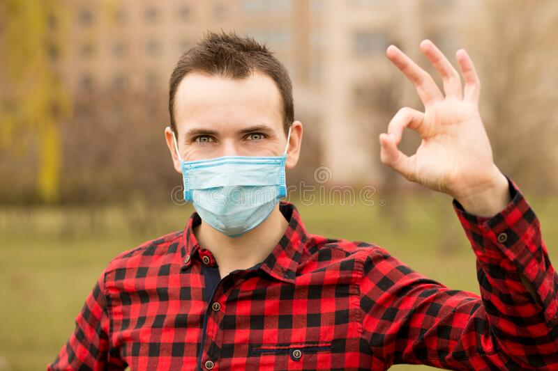 Serenity man wearing protective mask show gesture ok using hand up walk. Outdoor stock images