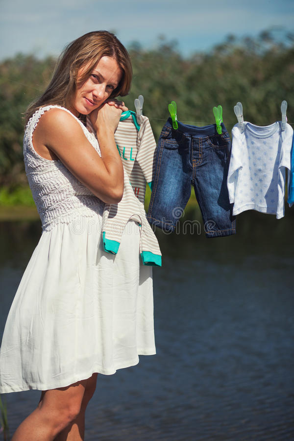 Serenity of a pregnant lady. Next to laundry line with baby clothes stock photos