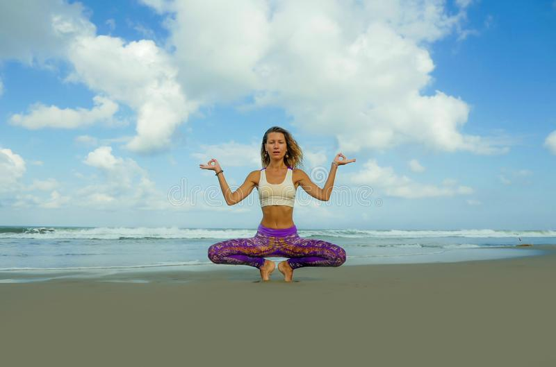 Young attractive and athletic woman in balance yoga posture at beautiful beach doing relaxation and meditation exercise under a royalty free stock photos