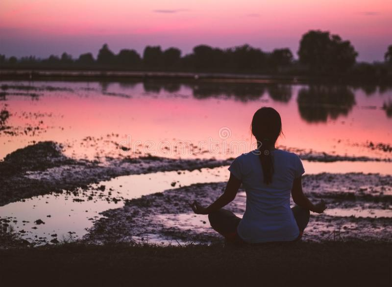 Serenity and yoga practicing, meditating at sunset background stock image