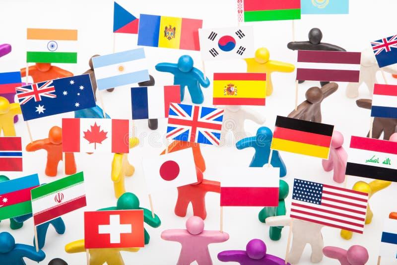 Seres humanos de la plastilina con las diversas banderas imágenes de archivo libres de regalías