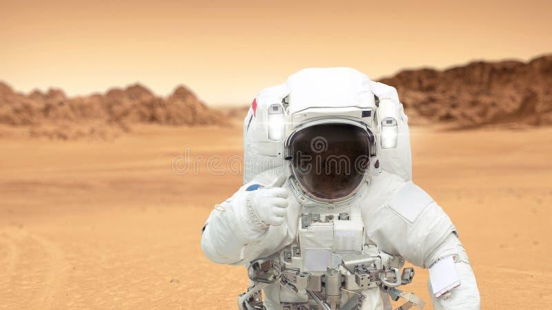 Seres humanos en el planeta Marte El astronauta en Marte muestra los pulgares-para arriba fotografía de archivo libre de regalías