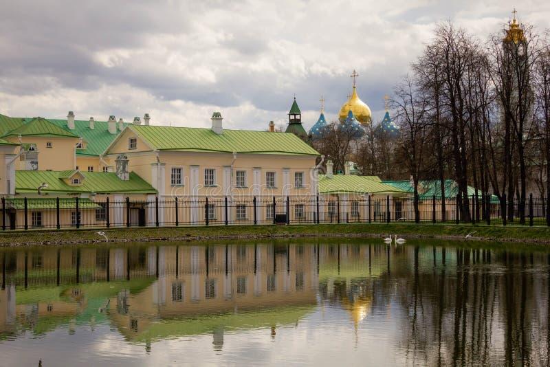 Sergiev Posad, Ryssland, Maj 2017 Vitt damm med två svanar på bakgrunden av forntida arkitektur på en molnig vårdag arkivbilder