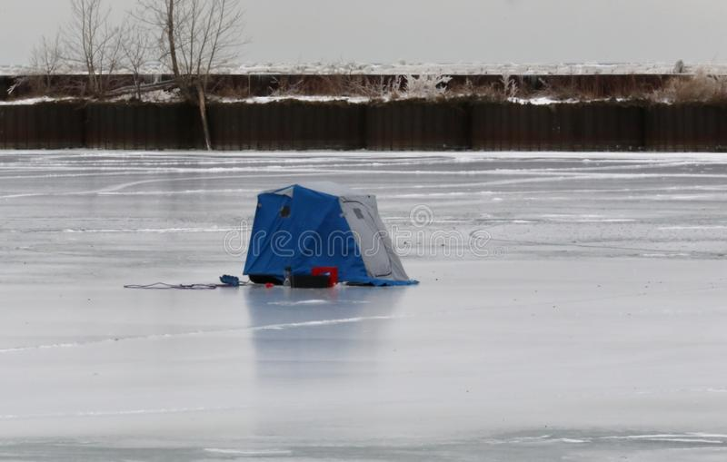 Ice fishing hut. Fishing hut sits on the frozen water keeping the fishermen warm from the cold weather royalty free stock photos