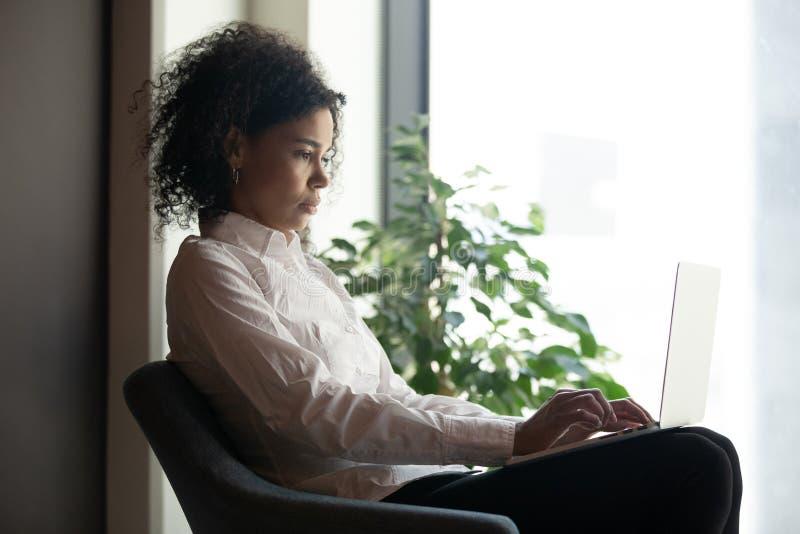 Seriös afrikansk affärskvinna som använder en bärbar dator på det moderna kontoret arkivfoto