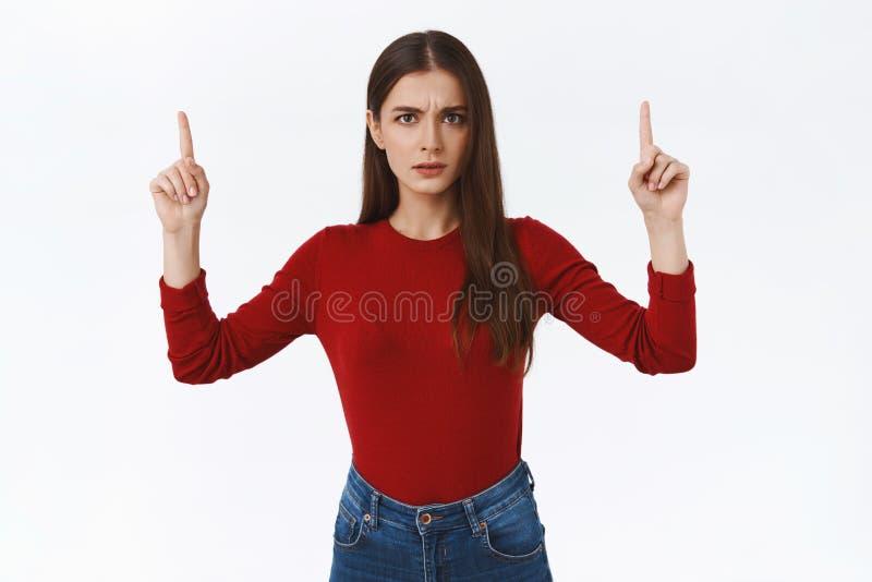 Seriös aussehend beunruhigt und besorgt frustrierte brunette Frau in rotem Pullover, starre zögerlich und besorgt Kamera und beso stockfotografie