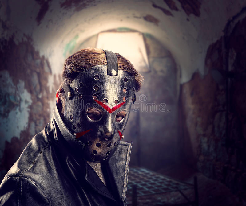 Serial maniac in hockey mask at torture chamber stock photography