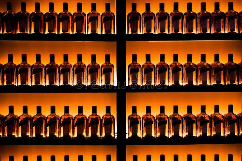 Serie av flaskor mot väggen royaltyfri foto