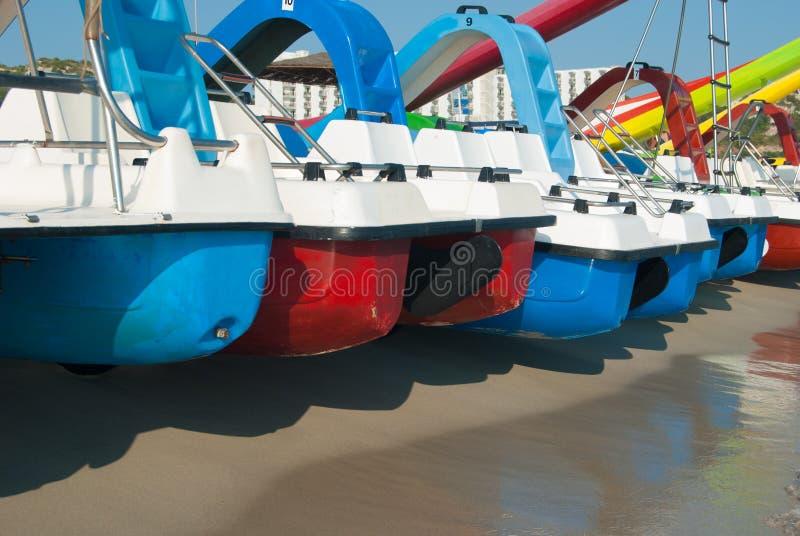 Serie barwione pedałowe łodzie na linii brzegowej zdjęcia royalty free