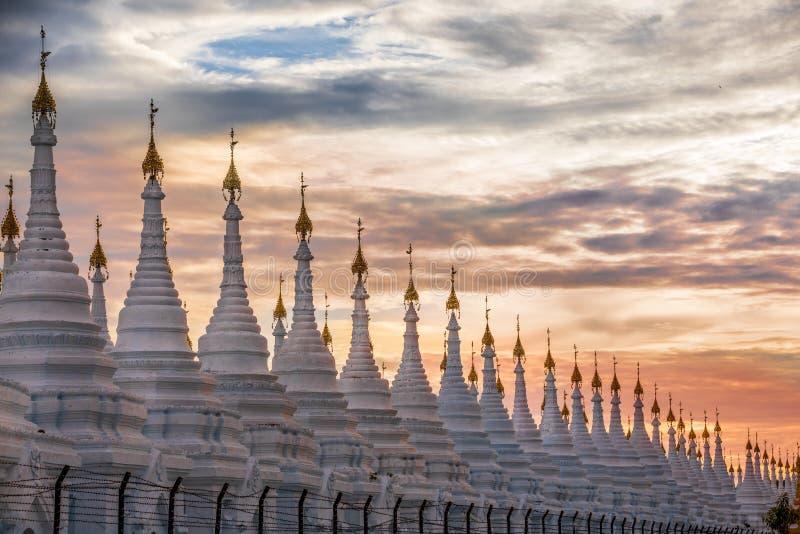Serie de la pagoda en línea en la puesta del sol en la región de Mandalay, Aungmyaythazan en Birmania imágenes de archivo libres de regalías