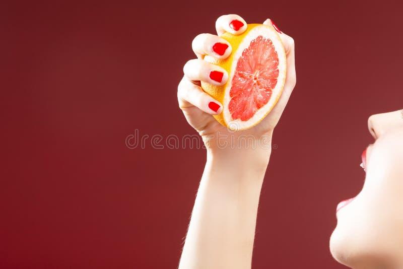Serie del frutto della passione Primo piano della mano della ragazza caucasica che schiaccia pompelmo immagine stock libera da diritti