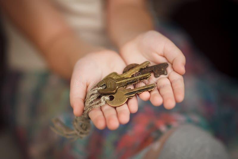 Serie della tenuta della bambina di vecchie chiavi immagini stock