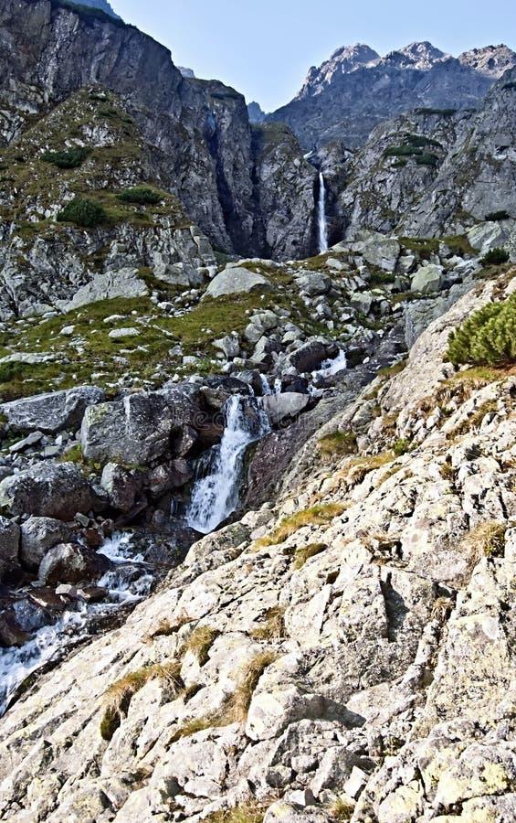 Serie di cascate con i picchi sui precedenti in alte montagne di Tatras fotografie stock