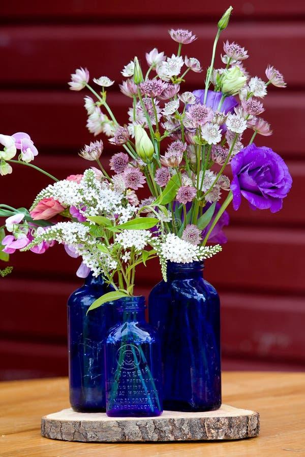 Serie di disposizione dei fiori di nozze Mazzo dei fiori per un evento di nozze in bottiglie blu fotografia stock