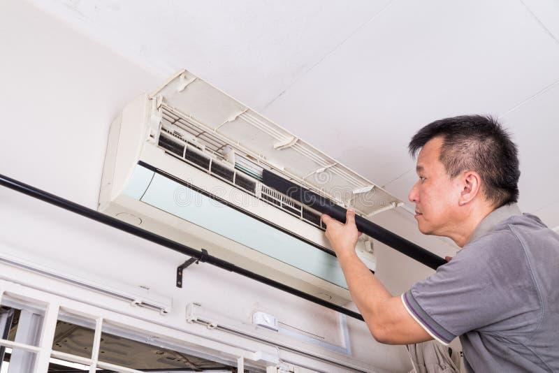 Serie di tecnico che assiste l'unità di condizionamento d'aria dell'interno fotografie stock libere da diritti