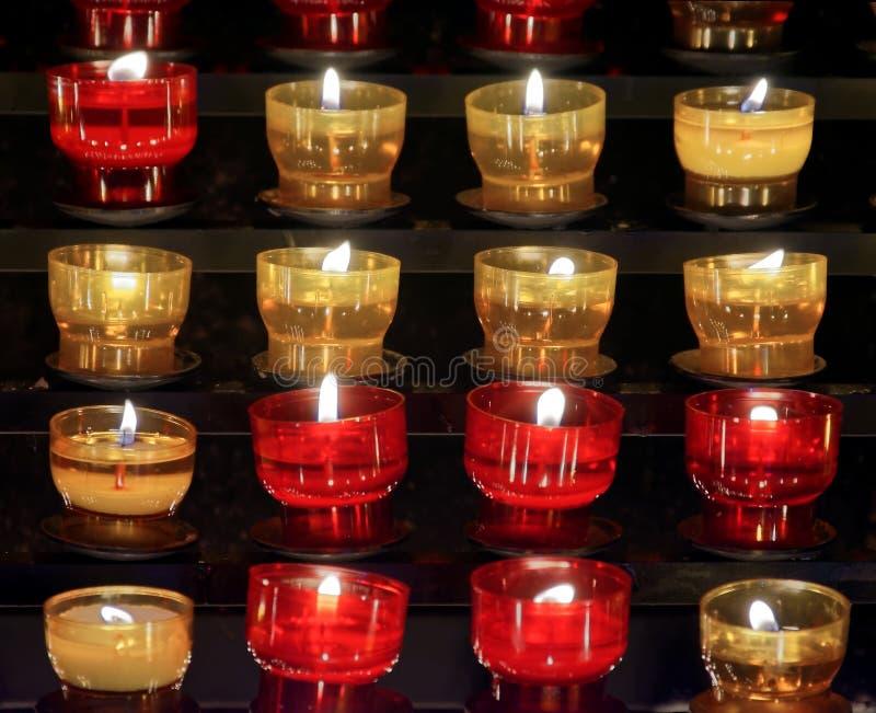 Serie wotywne świeczki zaświecali umieszczających inside małych szkła barwiony szkło czerwień i kolor żółty fotografia royalty free