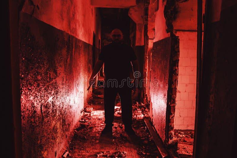 Seriell mördare med kniv i hand i röd korridor Brottscen och skräck skräckmaniak arkivfoto