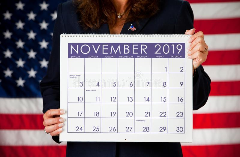 Politician: Holding a Calendar with November Election Day 2019. Series with an adult female in a suit, playing the part of a United States politician.  Different royalty free stock photo