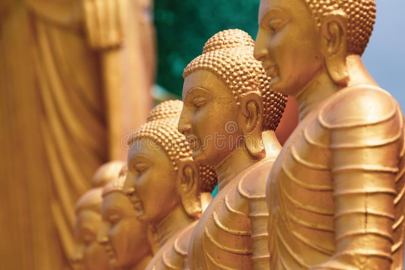 Series of Buddha statues. Face in the foreground, yellow gold sculptures. royalty free stock images