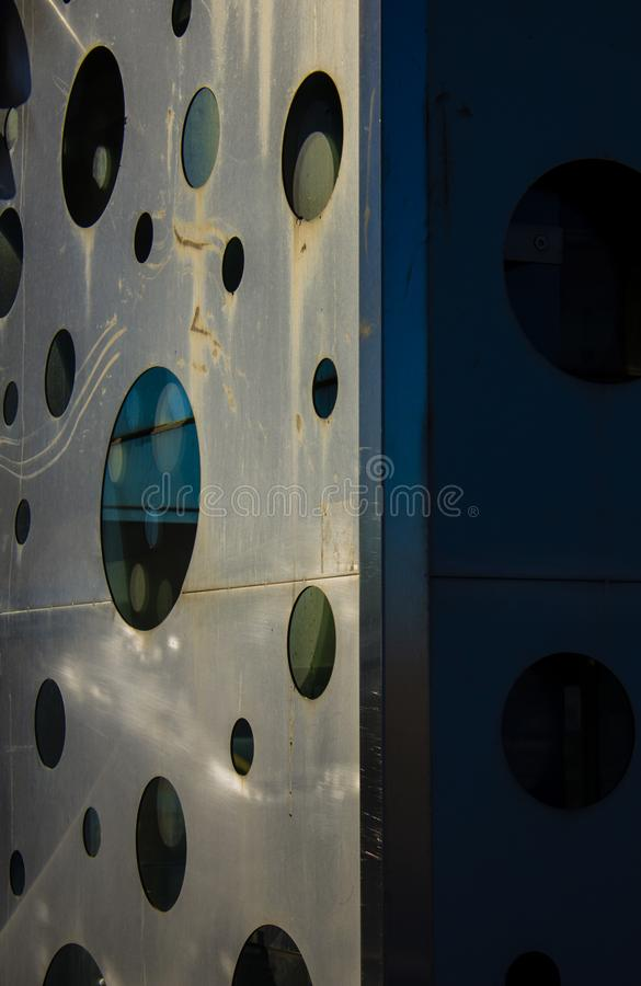 A series of glass windows openings on a steel surface with varied sizes stock photo