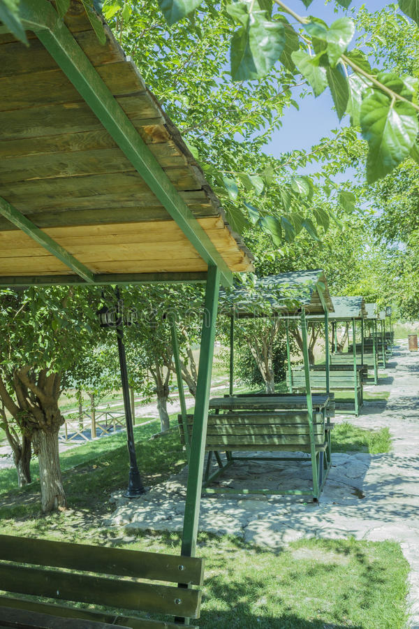 Series of green bench huts in a sunny outdoors park royalty free stock photography