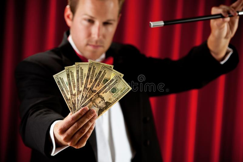 Magician: Going to Make Cash Disappear. Series about a magician in a traditional tuxedo, with various props, looking mysterious and magical royalty free stock photo