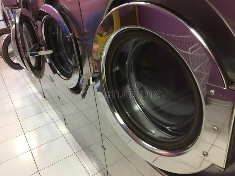 A series of metallic washing machines  in the self service laundry Pesaro, Italy,Europe. A series of metallic washing machines  in the self service laundry stock photos