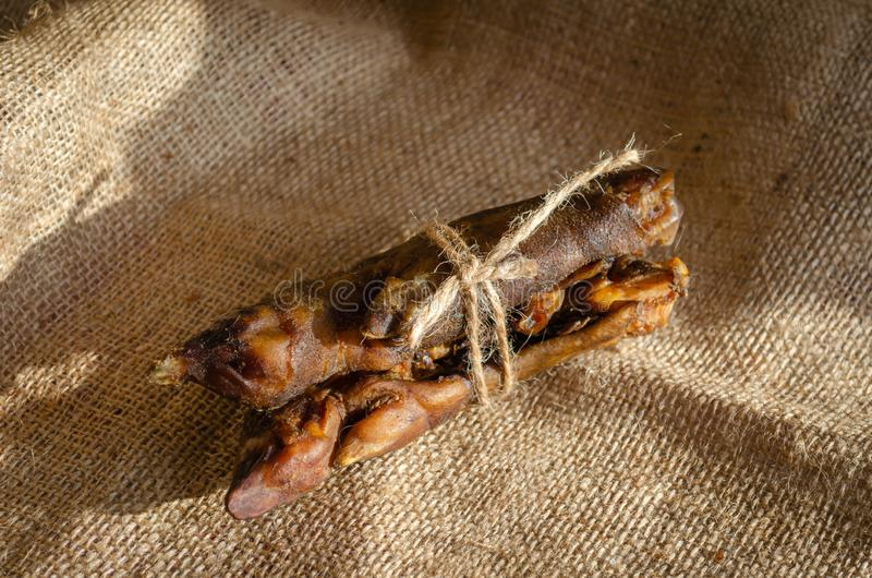 Two halves of a rope. Dried pork leg. Another angle Pork hoof. A series of natural treats for dogs stock photography