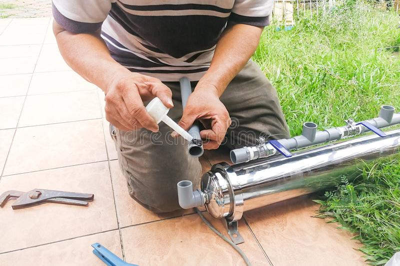Series of plumber fixing up outdoor water filter with pvc piping. Series of plumber fixing up outdoor water filter with glue on pvc piping stock images
