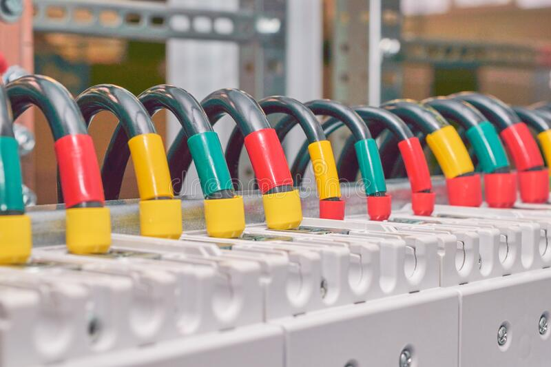 A series of several electrical wires connected to circuit breakers. A series of several electrical wires or cables connected to power circuit breakers in an stock photos
