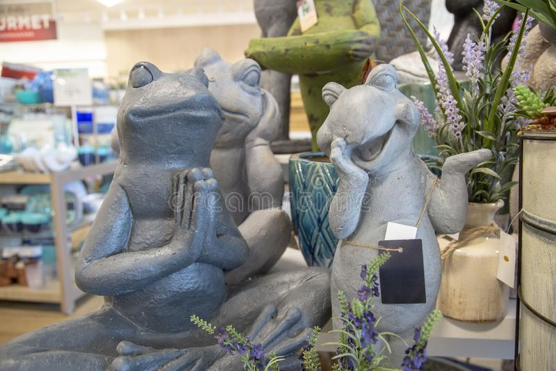 A series of stone frog statues in various poses. Inside a home décor store stock image