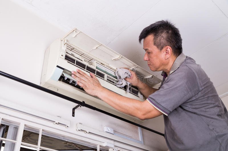 Series of technician servicing the indoor air-conditioning unit. Cleaning with cloth stock photos