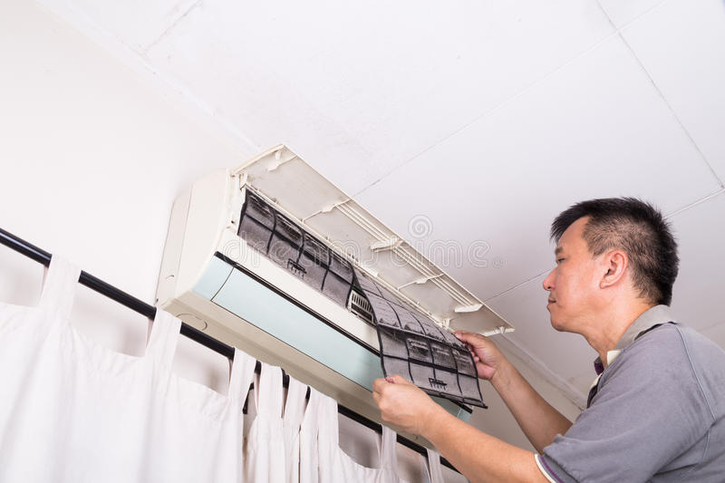 Series of technician servicing the indoor air-conditioning unit. Inspecting dust filter royalty free stock photo