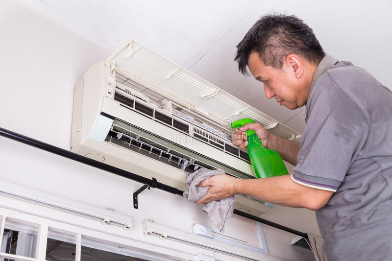 Series of technician servicing the indoor air-conditioning unit. Spraying chemical to remove deposits royalty free stock photography