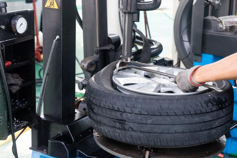 Series of worker removing tire from rim with removal machinery stock photo