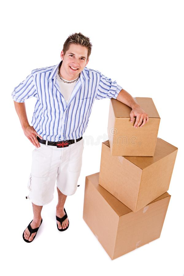 Student: Man Stands By Stack Of Packing Boxes royalty free stock photo
