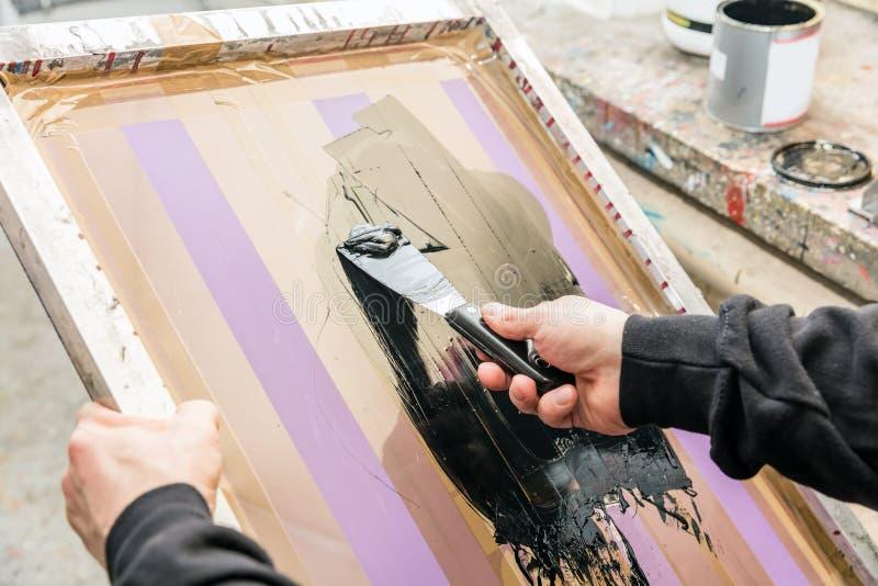 Serigrafía squeegeeing del hombre en un taller Serigrafía imágenes de archivo libres de regalías