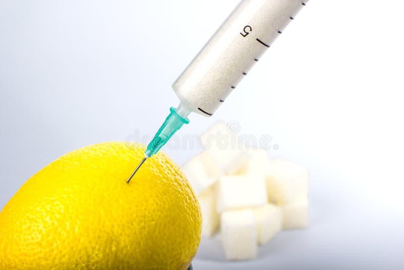 A seringa com o açúcar no limão fotos de stock