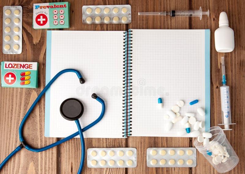 Seringa, estetoscópio, bloco de notas da página vazia, atadura, comprimido e luvas na tabela do doutor Diagnóstico médico ou pres fotografia de stock royalty free