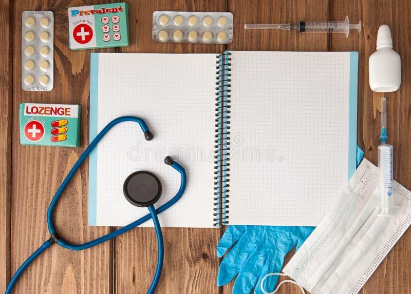 Seringa, estetoscópio, bloco de notas da página vazia, atadura, comprimido e luvas na tabela do doutor Diagnóstico médico ou pres foto de stock