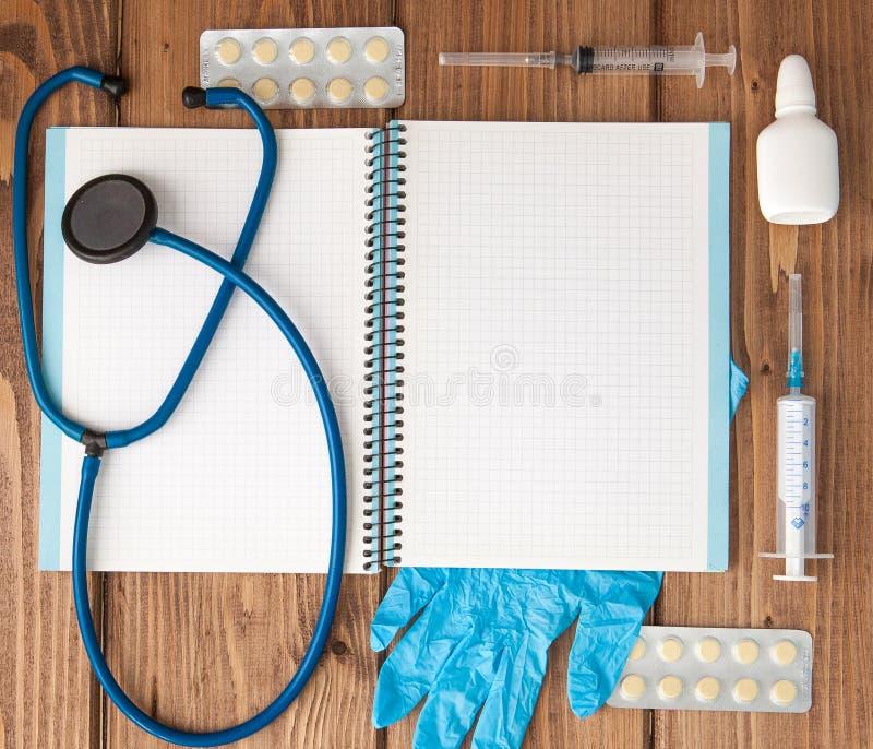 Seringa, estetoscópio, bloco de notas da página vazia, atadura, comprimido e luvas na tabela do doutor Diagnóstico médico ou pres fotos de stock