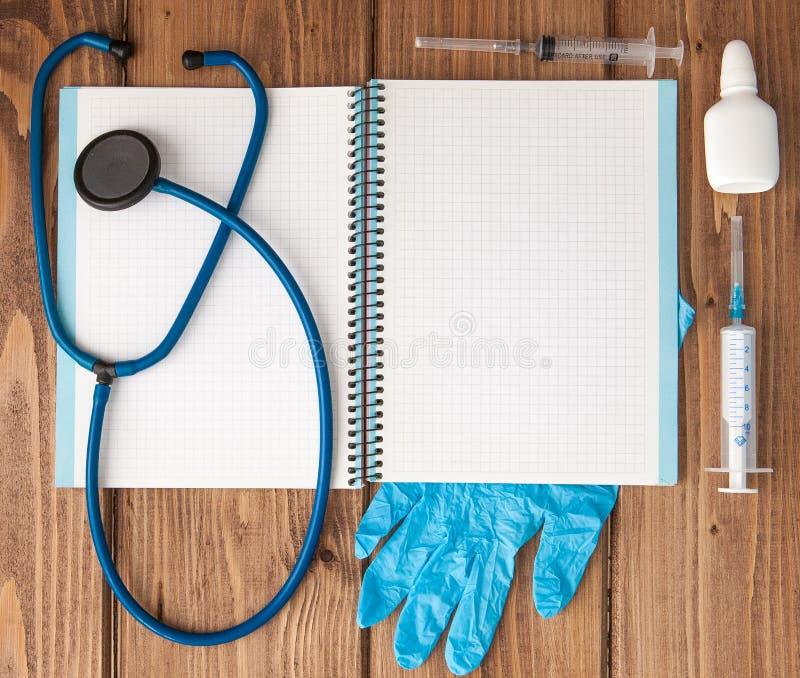 Seringa, estetoscópio, bloco de notas da página vazia, comprimido e luvas na tabela do doutor Diagnóstico médico ou modelo da pre imagem de stock