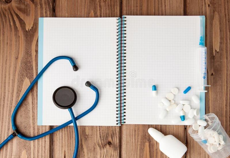 Seringa, estetoscópio, bloco de notas da página vazia e comprimido na tabela do doutor Diagnóstico médico ou modelo da prescrição imagens de stock royalty free