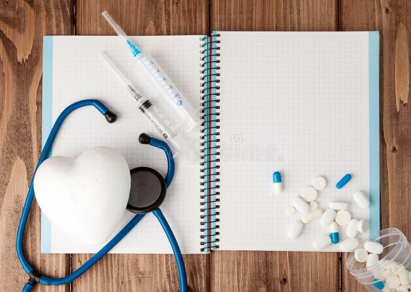 Seringa, estetoscópio, bloco de notas da página vazia e comprimido na tabela do doutor Diagnóstico médico ou modelo da prescrição imagem de stock