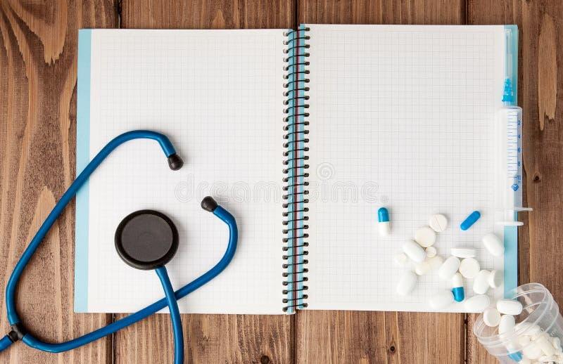 Seringa, estetoscópio, bloco de notas da página vazia e comprimido na tabela do doutor Diagnóstico médico ou modelo da prescrição fotografia de stock