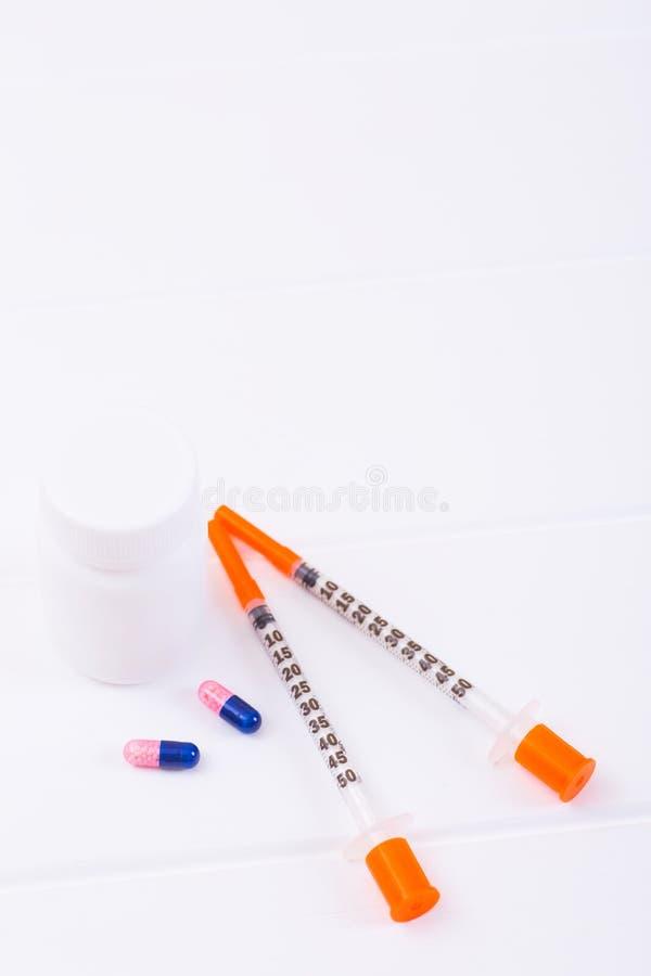 Seringas da insulina, duas cápsulas e garrafa plástica no fundo branco imagem de stock royalty free